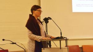 en kvinna står och talar i en sal