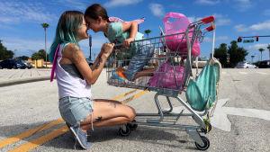 Pikkutyttö Moonee (Brooklynn Prince) on ostoskärryissä, äiti Halley (Bria Vinaite) kyykyssä vieressä