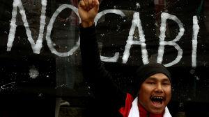 En manlig studerande protesterar mot en ny medborgarskapslag.