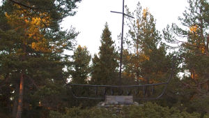 Monument av metall och sten som föreställer en båt med mast. Står bland träd i höstliga färger