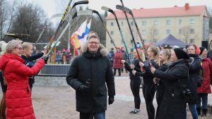 Jukka Jalonen kulkee jääkiekkomailojen ali Jukka Jalosen puiston nimiäisissä.