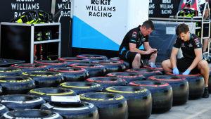 Två personer ur Williams personal sitter på några däck