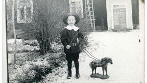 En pojke i finkläder leker med en trähäst i tömmar och med vidja som piska. På gårdsplan. 1880-1920-tal.
