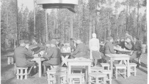 En svartvit gammal bild på en grupp militärklädda män som sitter utomhus runt bord och äter.