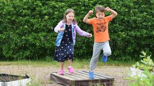 Maija och Erik Sallegren hoppar i en trädgård.