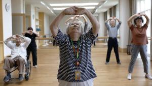 Kinesiska pensionärer tränar inomhus.