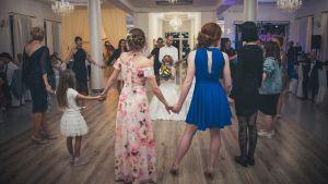 Festklädda personer står i ring och håller varandra i händerna. I mitten står en brudgum och håller händerna för ögonen på en brud som sitter på en stol.