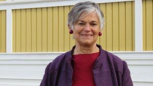 En kvinna med grått kort hår står framför ett gulmålat trähus (uncan i Ekenäs).