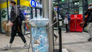 Samlingskärl för munskydd vid en metrostation.