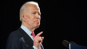 Joe Biden pekar i luften med sitt pekfinger i en talarstol.