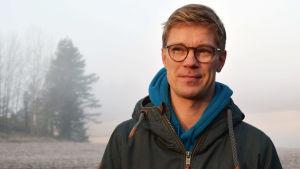 Jonas Lundberg står utomhus. I bakgrunden syns en dimmig åker.