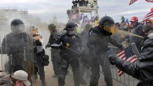 Poliser och Trumpanhängare utanför kongressbyggnaden i Washington den 6 januari 2021.