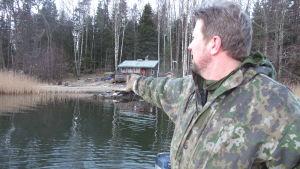 Person står i båt och pekar mot land