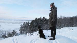 Man och hund blickar ut över vintrigt hav