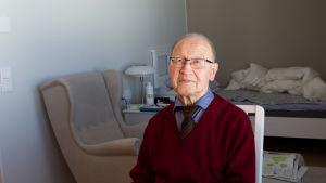 Eero Halonen istuu ja katsoo kameraan. Taustalla näkyy nojatuoli ja sijaamaton vuode.