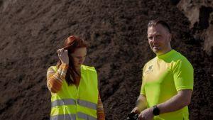 Nainen ja mies neonkeltaisissa työasuissa ison multakasan edessä.