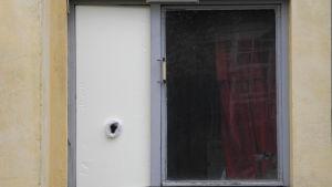 Kuva kerrostalon ikkunasta, jonka tuuletusaukkoa peittää stykoksilevy jossa on reikä ja sisällä on pimeää.