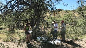 Harry Smith, Mary Joan Pierce och Richard Osburn står vid en vattenstation i öknen i Arizona.