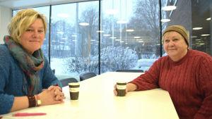 Regina Ekblom och Camilla Gorbatow sitter vid ett bord och dricker kaffe.