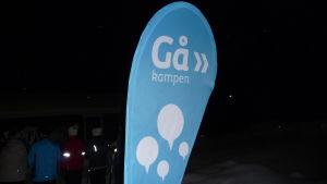 turkosfärgad gåkampen-skylt som finns ute i samband med en gåfest.