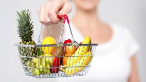 En shopping korg med frukt och bär.