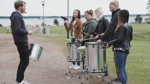 En grupp personer spelar samba på olika sorters trummor.
