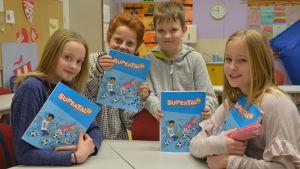 Sissi, Linus, Wolter och Emma sitter i klassrummet vid en pupet. De håller i sina matematikböcker, tittar in i kameran.
