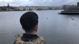 Bakhuvudet av en person med mörkt hår som tittar ut över vattnet.