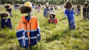 Hiljaisen kansan heinäpäinen hahmo päällään rakennustyöntekijän takki ja keltainen kypärä.