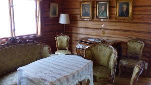 En med gult tyg klädd soffgrupp från 1700-talet, ett bord med vit bordduk, en antik byrålåda