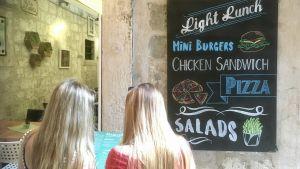 Två unga kvinnor tittar in i en restaurang.