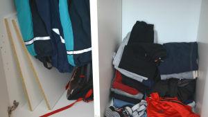Insidan av ett klädskåp. Till vänster står två hyllskivor lutade mot insidan av skåpet. De borde vara fästa på höger sida i skåpet där en hög med kläder istället ligger på skåpbottnen.