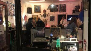 Litet konstgalleri med modern konst på väggarna och i fönstret och rätt mycket folk inne i lokalen.