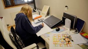 en flicka sitter och gör läxorna vid sitt skrivbord