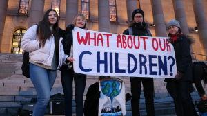 """Västnyländska elever med en skylt med texten """"What about our children?""""."""