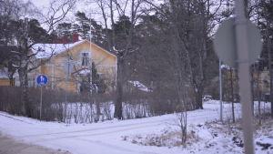 Vägkorsning på vintern, i bakgrunden ett gult trähus.