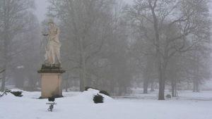 En staty av en kvinna i dimmigt och vintrigt landskap. Träd i bakgrunden.