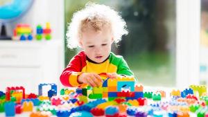 Ett barn sitter vid ett bord och bygger med olika klossar.