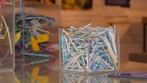 några glasskålar (formade som kuber) fyllda med plastskräp. I den närmast kameran finns gamla vaddpinnar. Vaddet har lossnat, kvar finns pinnen av plast.