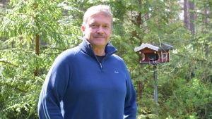 En man i blå tröja poserar i en grön, skogsliknande trädgård. Bakom finns ett fågelbräde som är som ett rött hus.
