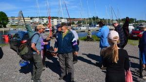 En grupp människor står och pratar i solen vid Borgå å.