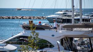 Tre personer sitter ute på en båt i solen.