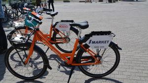 Två orange cyklar står på ett torg.