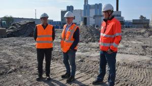 Tre män i byggvästar på byggarbetsplats.