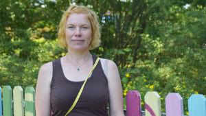 En kvinna med rött lockigt hår i brunt linne. I bakgrunden syns grön skog och ett staket.