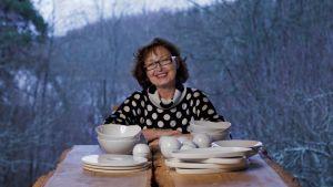 Kvinna med mörkt lockigt hår och glasögon sitter vid bord med keramik och ler.