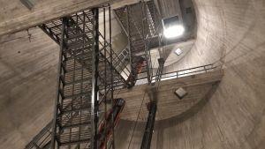 Metalltrappor går sick-sack över bilden uppåt mellan de grå betongväggarna.