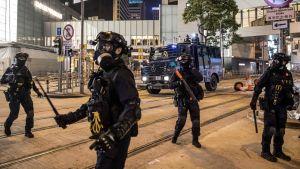 Poliser med batonger på gata i Hongkong.