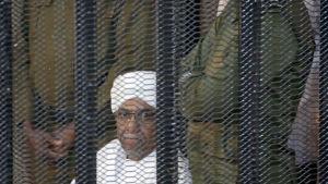 Sudanin entinen presidentti Omar al-Bashir seuraa oikeudenkäyntiään vankikopista Khartoumissa.