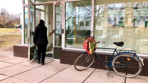 En svartklädd kvinna med väska i handen går in genom en glasdörr. Utanför står en blå herrcykel.